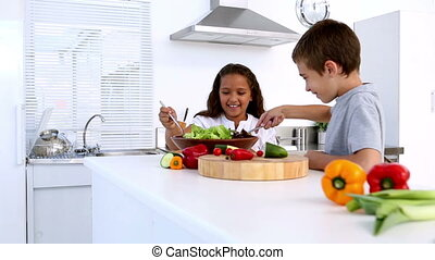 Siblings preparing salad together at home in kitchen