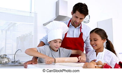 Father watching son roll pastry with sister at home in...
