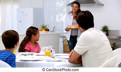 Mother bringing pizza to dinner table at home in kitchen