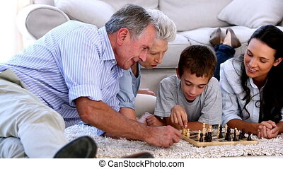 Extended family playing chess together on the floor at home