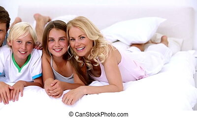Cute family smiling at the camera lying on bed together