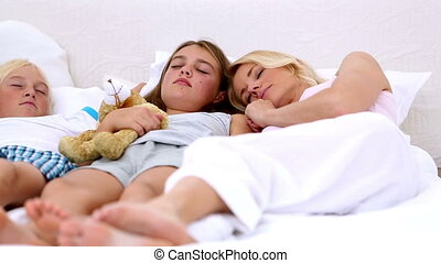 Parents dozing with their children at home in bedroom