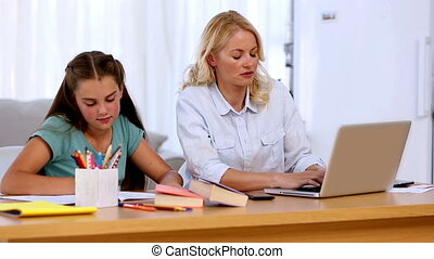 Mother working on laptop with daughter doing homework at...