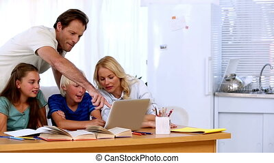 Family using the laptop together to do homework at desk in...