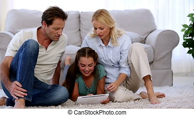 Parents and daughter using tablet on floor of living ro