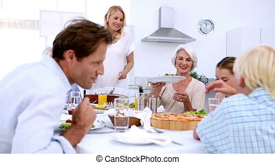Woman serving salad at dinner to extended family at home in...