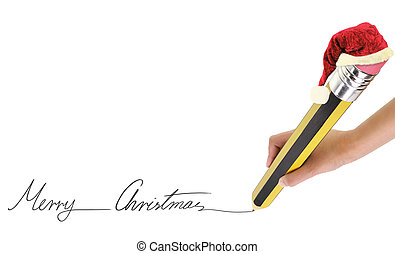 Hand holding a big pencil and writing Merry Christmas on...