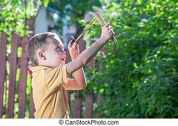 slingshot - young boy with slingshot shooting