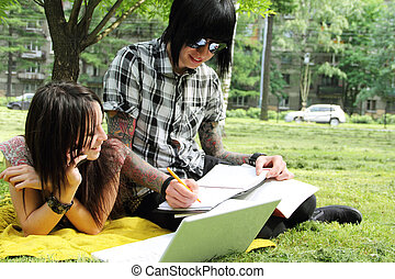Couple studying outdoors - Couple of young students studying...