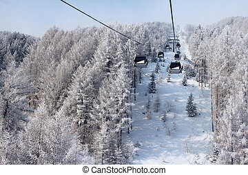 Chair lift between beautiful firs in winter mountains forest