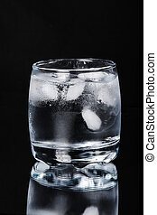 Glass of water with ice on a black background