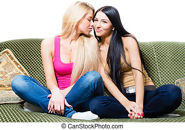 Portrait of two pretty young girlfriends or sisters sitting together