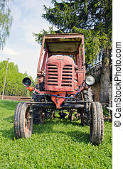 old red tractor on grass in farm