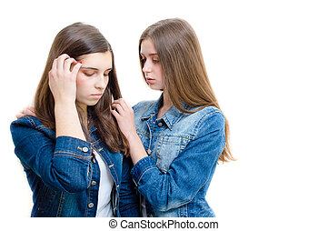 Two beautiful young women comforting one another on white...