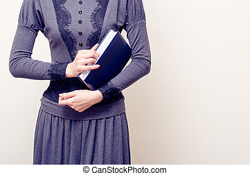 Young beautiful woman in gray vintage dress holding bible...