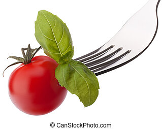 Basil leaf and cherry tomato on fork isolated on white...