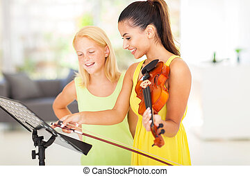 pretty music teacher pointing notes to student