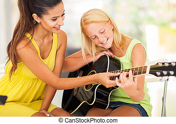 beautiful music teacher tutoring young girl to play guitar -...