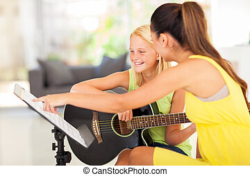guitar lesson - young preteen girl having guitar lesson at...