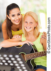 friendly teacher with her music learner - portrait of...