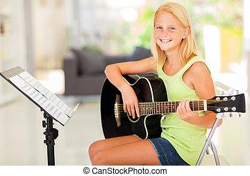 preteen girl practicing guitar - cheerful preteen girl...