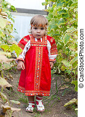Little girl in Russian national dress collects cucumbers in...