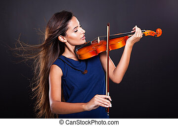 beautiful woman playing violin on black background