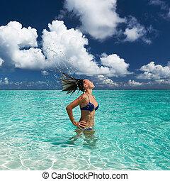 Woman splashing water with hair in the ocean - Woman...