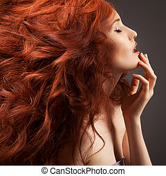 Beautiful woman with curly hairstyle against gray background...