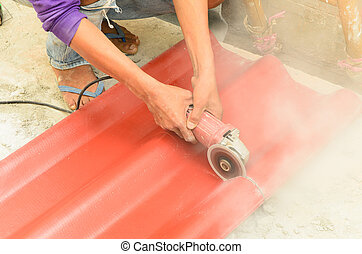 Cutting the roof tile - Contractor cutting a red roof tile