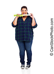 overweight woman eating celery