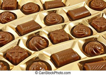 Chocolate sweets in golden box - Chocolate sweets in an open...