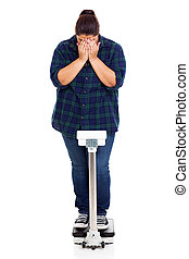 unhappy overweight girl crying when weighting on scale