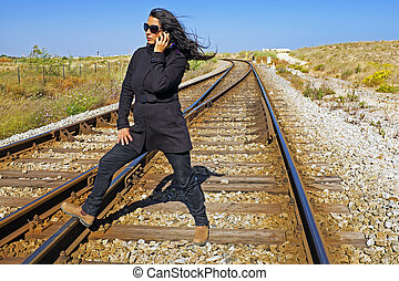 Woman phoning on a railroad track