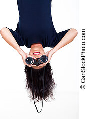 upside down woman holding binoculars - upside down photo of...