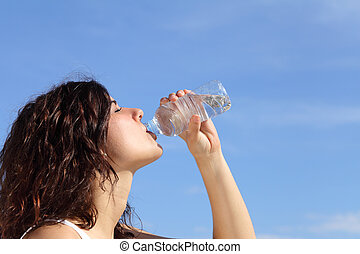 Profile of a woman drinking water from a plastic bottle with...