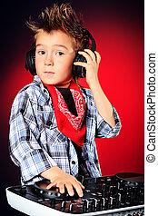 handsome - Expressive little boy DJ in headphones mixing up...
