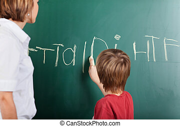 Young boy writing on the blackboard with chalk watched by...