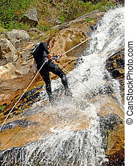 Men descending on rappel - Men descending waterfall in...
