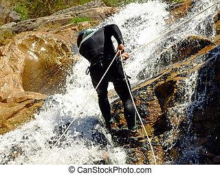 Men descending on rappel - Men descending waterfall in...
