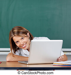 Woman with laptop - Smiling teacher posing with laptop on...