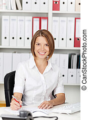 Smiling woman sitting at her desk