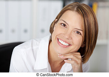 Portrait of a pretty smiling woman at the office with her...
