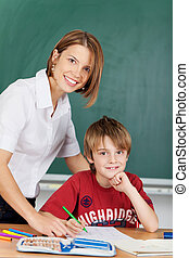 Teacher and elementary school student - Smiling teacher and...