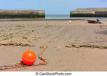 Orange boat marker and motorboat in a low tide harbor
