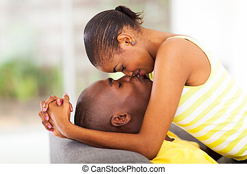 young african american couple kissing and flirting