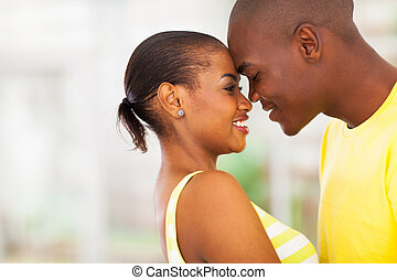 young african american couple flirting - close up portrait...