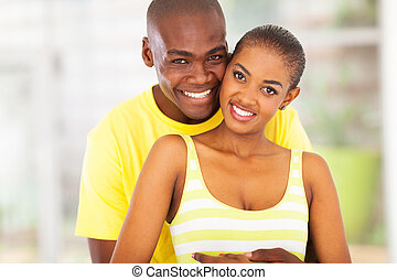 young african couple hugging each other - cheerful young...
