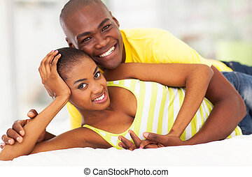 loving african american couple lying in bed