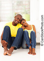 young african couple sitting on the bedroom floor - cheerful...